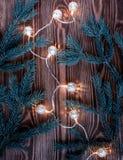 Kerstmissamenstelling met uitstekende slinger en blauwe spartakken op houten achtergrond koordlichten Stock Fotografie