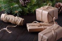 Kerstmissamenstelling op houten achtergrond met boom, denneappels en kartondozen Royalty-vrije Stock Fotografie