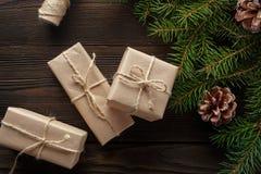 Kerstmissamenstelling op houten achtergrond met boom, denneappels en kartondozen Stock Fotografie