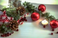 Kerstmissamenstelling op houten achtergrond met Kerstmisballen en groene takkerstboom met denneappels, brandende kaars Stock Afbeeldingen