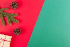 Kerstmissamenstelling op rode en groene achtergrond Groene sparrentak, denneappels en huidige doos Royalty-vrije Stock Foto's