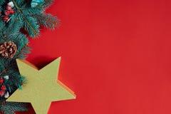 Kerstmissamenstelling van denneappels, nette takken en stapel giftdozen op rode achtergrond Stock Afbeeldingen