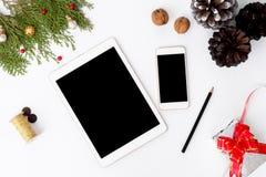 Kerstmissamenstelling van tabletsmartphone Kerstmisgiften en decoratie op witte achtergrond Vlak leg hoogste mening stock afbeelding