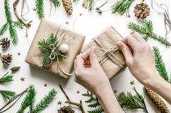 Kerstmissamenstelling voor de voorbereiding voor het Nieuwjaar De meisjes` s handen binden een boog op de giftomslag Royalty-vrije Stock Afbeelding