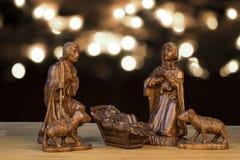 Kerstmisscène met beeldjes Baby Jesus, Mary, Joseph op ligh Royalty-vrije Stock Afbeeldingen