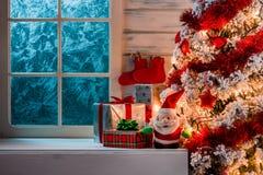 Kerstmisscène met boomgiften en bevroren venster Stock Foto
