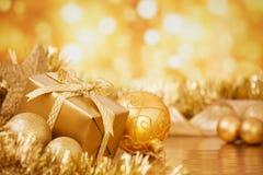 Kerstmisscène met gouden snuisterijen en gift, gouden achtergrond Royalty-vrije Stock Foto