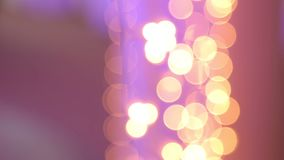 Kerstmisslinger met Gouden en purpere lichten, close-up Bokeh stock video