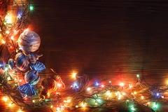 Kerstmisslingers van lampen op een houten achtergrond Stock Afbeeldingen