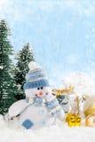 Kerstmissneeuwman met giften op sneeuwachtergrond Stock Afbeeldingen
