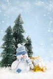 Kerstmissneeuwman met giften op sneeuwachtergrond Stock Foto