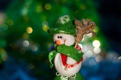 Kerstmissneeuwman op de achtergrond van vage lichten groene boom Royalty-vrije Stock Foto's