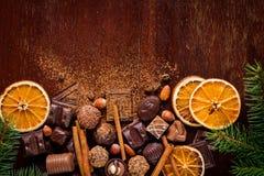 Kerstmissnoepjes: chocolade, pralines, droge oranje ringen, kruiden en noten Royalty-vrije Stock Foto's
