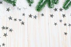 Kerstmisspar in sneeuw met zilveren sterren op witte houten achtergrond Royalty-vrije Stock Foto