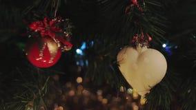 Kerstmisspeelgoed die op Kerstmisboom slingeren, rood en wit, vrouwen hangend speelgoed stock videobeelden