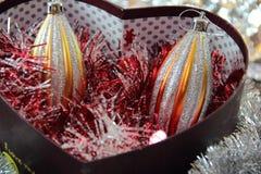 Kerstmisspeelgoed in een doos in de vorm van een hart Stock Fotografie