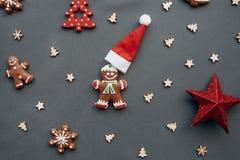 Kerstmisspeelgoed en peperkoek in de vorm van een traditionele gembermens met een Santa Claus-hoed op een grijze achtergrond royalty-vrije stock afbeelding