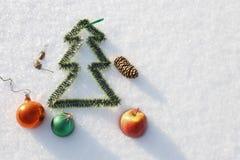 Kerstmisspeelgoed op de sneeuw, door de zon in een de winterdag die wordt aangestoken Royalty-vrije Stock Afbeeldingen