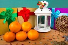 Kerstmisstilleven, mandarijnen, dozen met giften, lantaarn, houten achtergrond, Kerstmisachtergrond Stock Foto