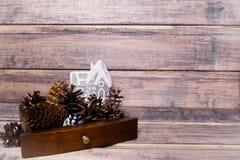 Kerstmisstilleven met kegels en een stuk speelgoed huis Stock Afbeelding