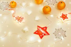 Kerstmisstilleven met vakantielichten Mandarijnen, houten decoratie rode sterren, Kerstboom, zilveren sneeuwvlokken, wit glas Stock Afbeelding