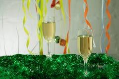 Kerstmisstilleven - Twee glazen mousserende wijn met blauwe Kerstmisballen en klatergoud op Kerstboomachtergrond stock foto's