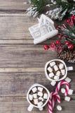 Kerstmisstilleven - twee koppen van hete chocolade met heemst, suikergoed, stuk speelgoed huis en tak van spar met bessen Stock Afbeelding