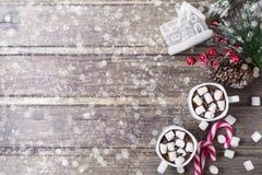 Kerstmisstilleven - twee koppen van hete chocolade met heemst, suikergoed, stuk speelgoed huis en tak van spar met bessen Royalty-vrije Stock Foto's