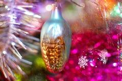 Kerstmisstuk speelgoed in de vorm van graan op een achtergrond van een helder fonkelend multi-colored klatergoud stock foto