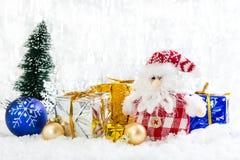 Kerstmisstuk speelgoed sneeuwman met giften op sneeuwachtergrond Stock Afbeeldingen
