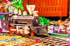Kerstmisstuk speelgoed spoorweg dichtbij een Kerstboom met lichten Royalty-vrije Stock Afbeelding