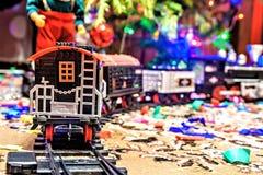 Kerstmisstuk speelgoed spoorweg dichtbij een Kerstboom met lichten Royalty-vrije Stock Foto's