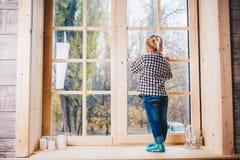 Kerstmistak en klokken Een kind met blondehaar in warm sokken, jeans en overhemd bevindt zich met haar die terug op windowstick,  Stock Afbeeldingen