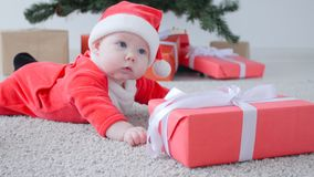 Kerstmistak en klokken Leuke Baby in kostuum die van Santa Claus, een gift kijken stock video