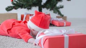 Kerstmistak en klokken Leuke Baby in kostuum die van Santa Claus, een gift kijken stock videobeelden