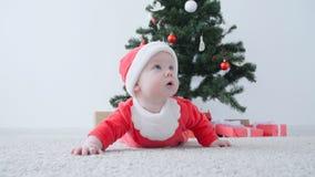 Kerstmistak en klokken Leuke Baby in kostuum die van Santa Claus, een gift kijken stock footage