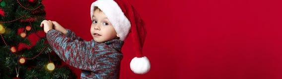 Kerstmistak en klokken Nieuw jaar kindkleding omhoog een Kerstboom Jonge geitjes en Kerstmisspeelgoed royalty-vrije stock foto