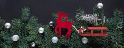 Kerstmistak en klokken Vakantiekaart met nieuwe jaardecoratie, herten, sneeuwvlokken, sparrentakken en ballen op zwarte achtergro Stock Afbeelding