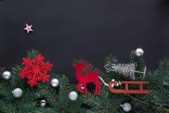 Kerstmistak en klokken Vakantiekaart met nieuwe jaardecoratie, herten, sneeuwvlokken, sparrentakken en ballen op zwarte achtergro Stock Foto