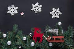 Kerstmistak en klokken Vakantiekaart met nieuwe jaardecoratie, herten, sneeuwvlokken, sparrentakken en ballen op zwarte achtergro Stock Foto's