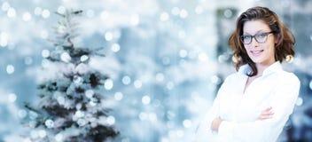 Kerstmisthema, bedrijfs glimlachende vrouw op vage verstralers Stock Afbeeldingen