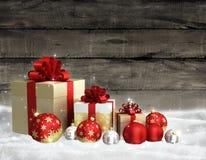 Kerstmisthema met glasballen en giftvakje op houten muur als achtergrond en vrije ruimte voor tekst Stock Foto's
