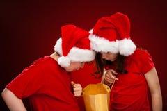 Kerstmistijd - meisje en jongen met Santa Claus Hats royalty-vrije stock afbeeldingen