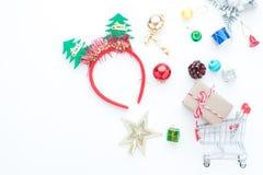 Kerstmistoebehoren en boodschappenwagentje met giftdozen op wit Stock Afbeeldingen