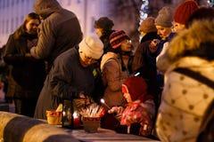 Kerstmistraditie: mensen lichte kaarsen in de avond van Komst Stock Foto's