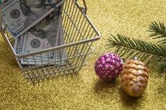 Kerstmisuitgaven/vakantiedecortions en de dollars van Verenigde Staten in het boodschappenwagentje/het concept Royalty-vrije Stock Afbeeldingen