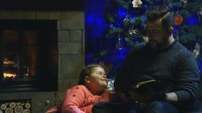 Kerstmisverhaal van de mensenlezing aan dochter stock video