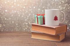 Kerstmisviering met kop en giftvakje op boeken over bokehachtergrond Stock Afbeelding