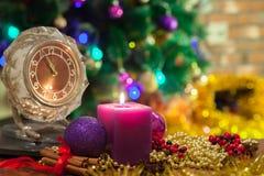 Kerze, alte Uhr und Weihnachtsbälle mit Winterdekoration Stockfotos