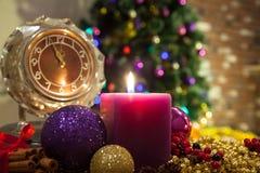 Kerze, alte Uhr und Weihnachtsbälle mit Winterdekoration Stockfotografie